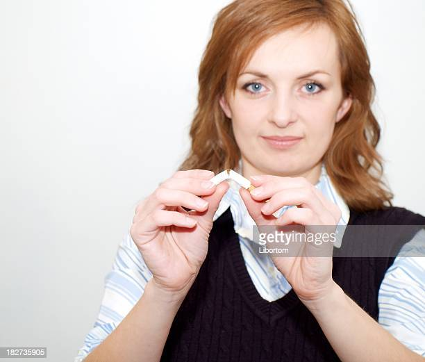 Woman breaking a cigarette symbolizing no more smoking