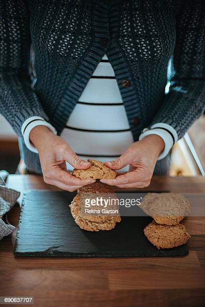 woman breaking a cookie in half - rekha garton stock pictures, royalty-free photos & images