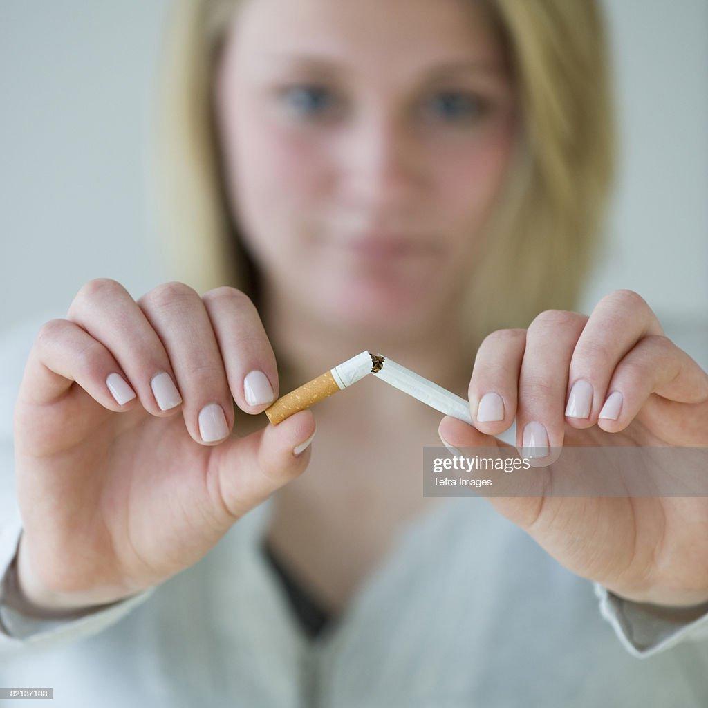 Woman breaking cigarette : Stock Photo
