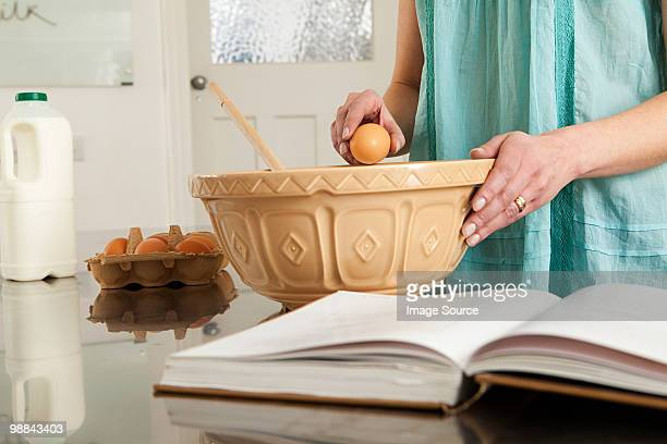 Woman breaking egg into bowl