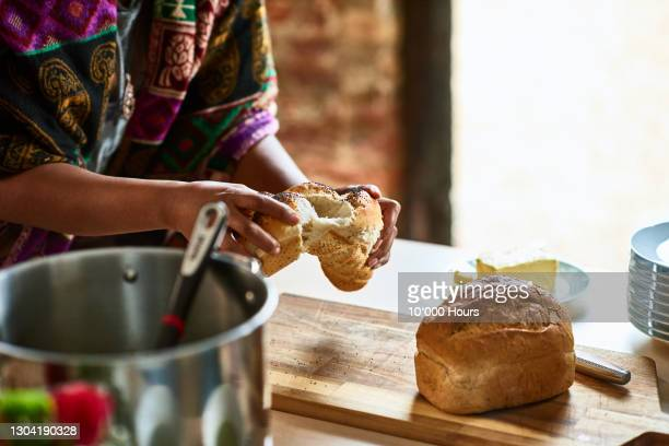 woman breaking freshly baked bread - hand stock pictures, royalty-free photos & images