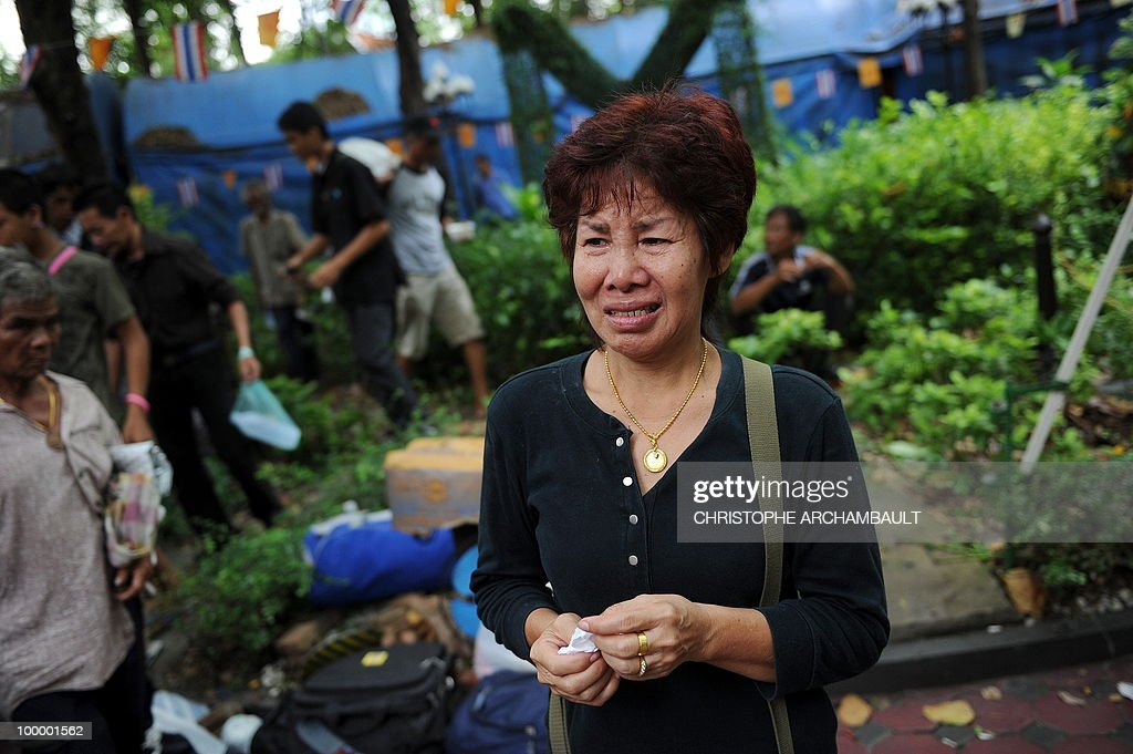A woman breaks down as looking at the dead bodies of anti-government protesters killed in a gunbattle the day before at a temple which had been turned into a shelter within an anti-government protest site in downtown Bangkok on May 20, 2010. Gunshots rang out near a Buddhist temple in the heart of an anti-government protest zone in Bangkok, and soldiers were advancing on foot along an elevated train track, an AFP photographer saw. Thai security forces stormed the 'Red Shirts' protest camp on May 19 in a bloody assault that forced the surrender of the movement's leaders who asked their supporters to disperse. AFP PHOTO/Christophe ARCHAMBAULT