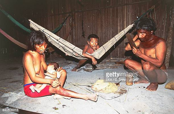 A woman breastfeeding her child and a man cleaning his face of ritual decoration Yanomami Indians from the Cavaroa tribe near the Siapa River...