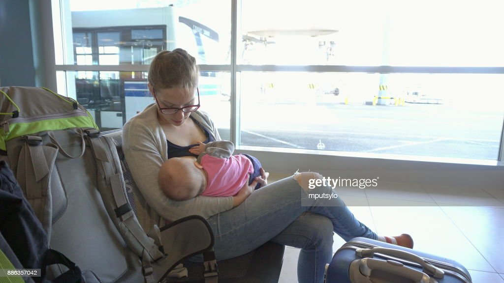 A Woman Breastfeeding her Child at the Airport : Stock Photo
