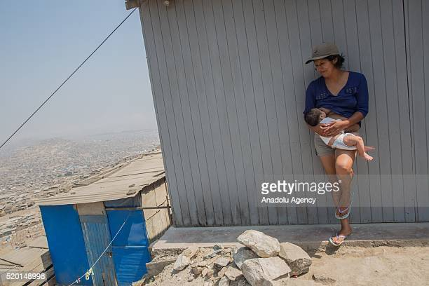 A woman breastfeeds her baby in San Juan de Miraflores district of Lima Peru on April 9 2016 In advance of the general elections of April 10 the...