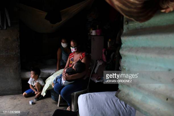 TOPSHOT A woman breastfeeds her child next to her motherinlaw in their house in La Brigada neighbourhood in Guatemala City where people are hanging...