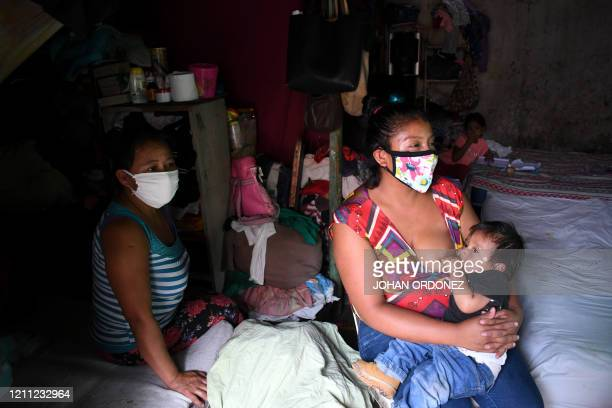 A woman breastfeeds her child next to her motherinlaw in their house in La Brigada neighbourhood in Guatemala City where people are hanging or waving...