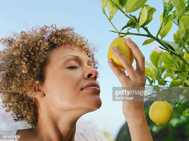Woman breathes scent of fresh lemon