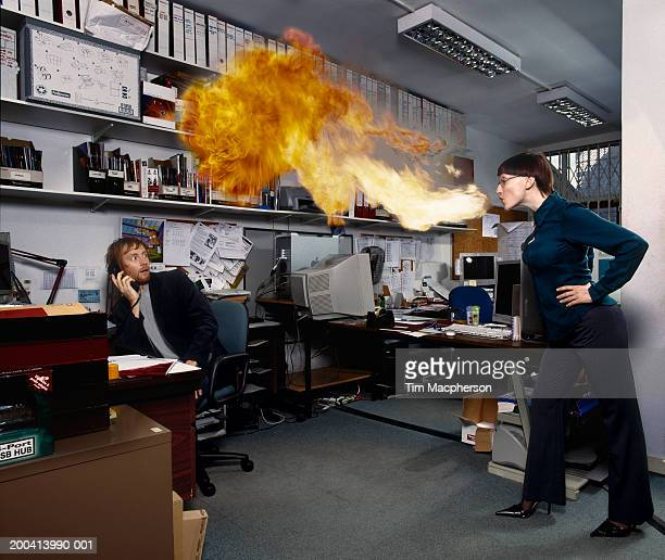 Woman breathing fire over man sitting in office (Digital Composite)