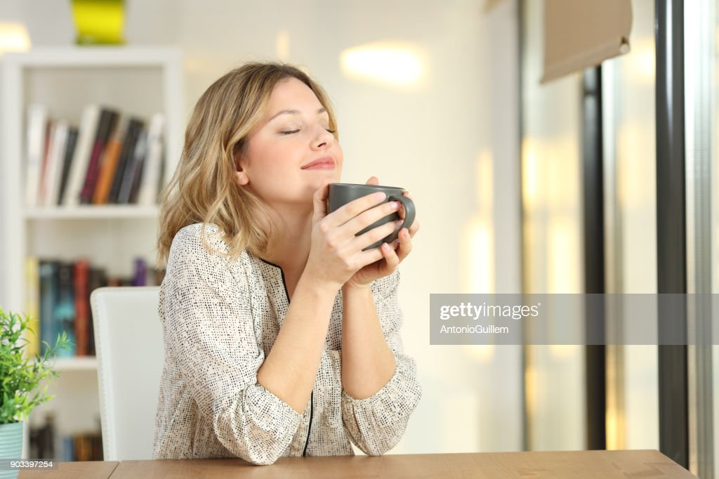 Woman breathing holding a coffee mug at home : Stock Photo