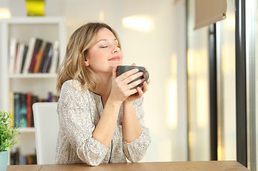 Woman breathing holding a coffee mug at home 903397254