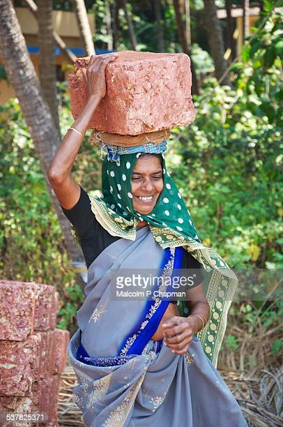 Woman brick carrier, builder, Kerala, India