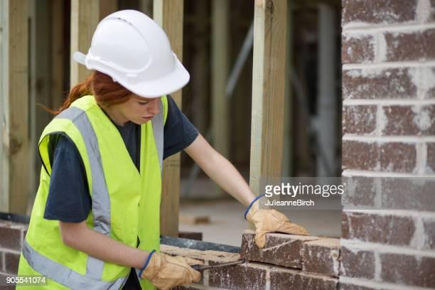 Woman bricklayer preparing laying bricks on wall