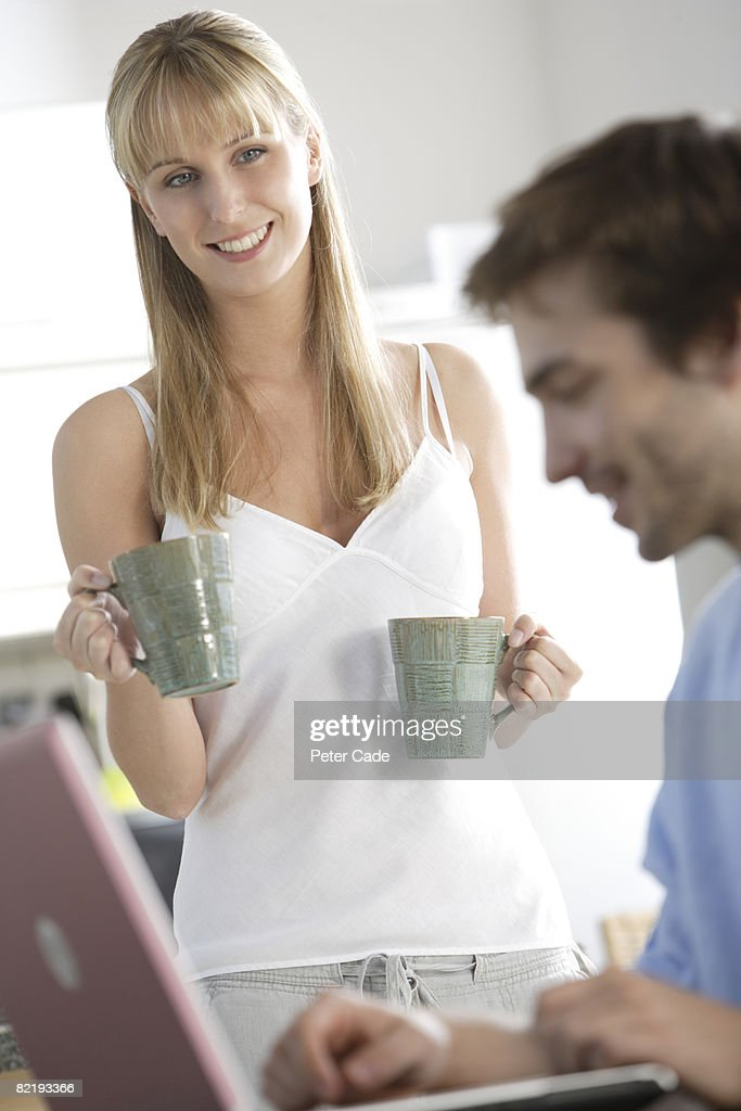 Woman bring drink to man on laptop : Stock Photo