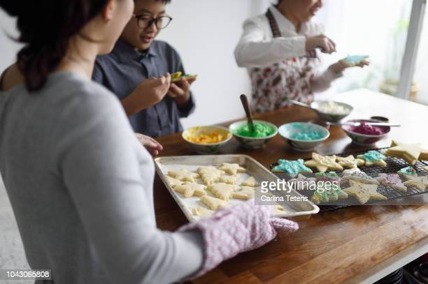 woman bringing a fresh tray of cookies to her kids icing - tradition stock pictures, royalty-free photos & images