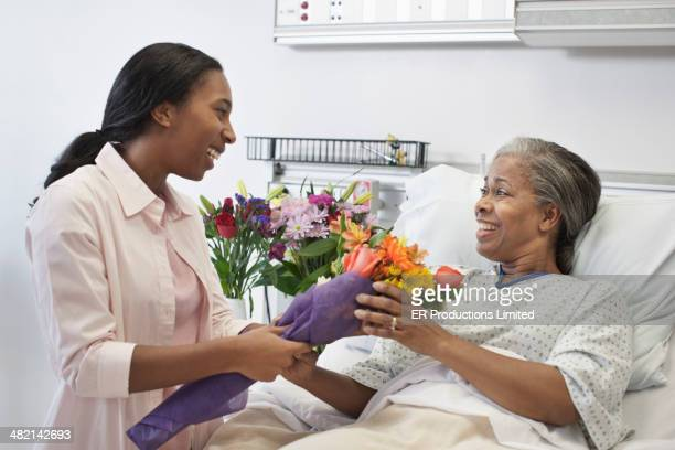 Woman bringing mother flowers in hospital