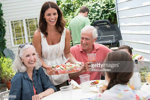 Woman bringing salad into outdoors table