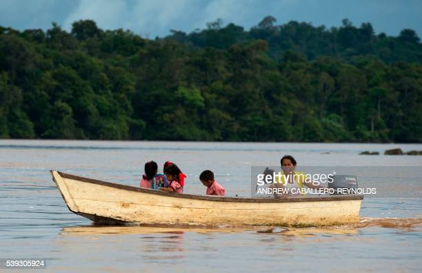 A woman brings children home from school on a boat near the town of Bartica Guyana on June 6 2016 Bartica is a town at the confluence of two major...