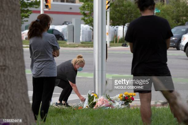 Woman brings flowers and pays her respects at the scene where a man driving a pickup truck struck and killed four members of a Muslim family in...