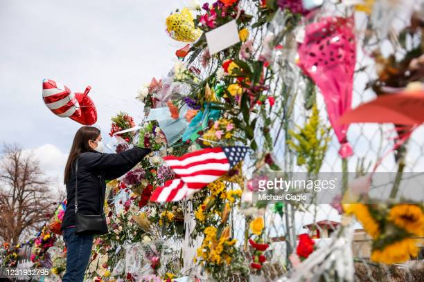 Woman brings flowers to a makeshift memorial outside a King Soopers grocery store on March 25, 2021 in Boulder, Colorado. Ten people, including a...