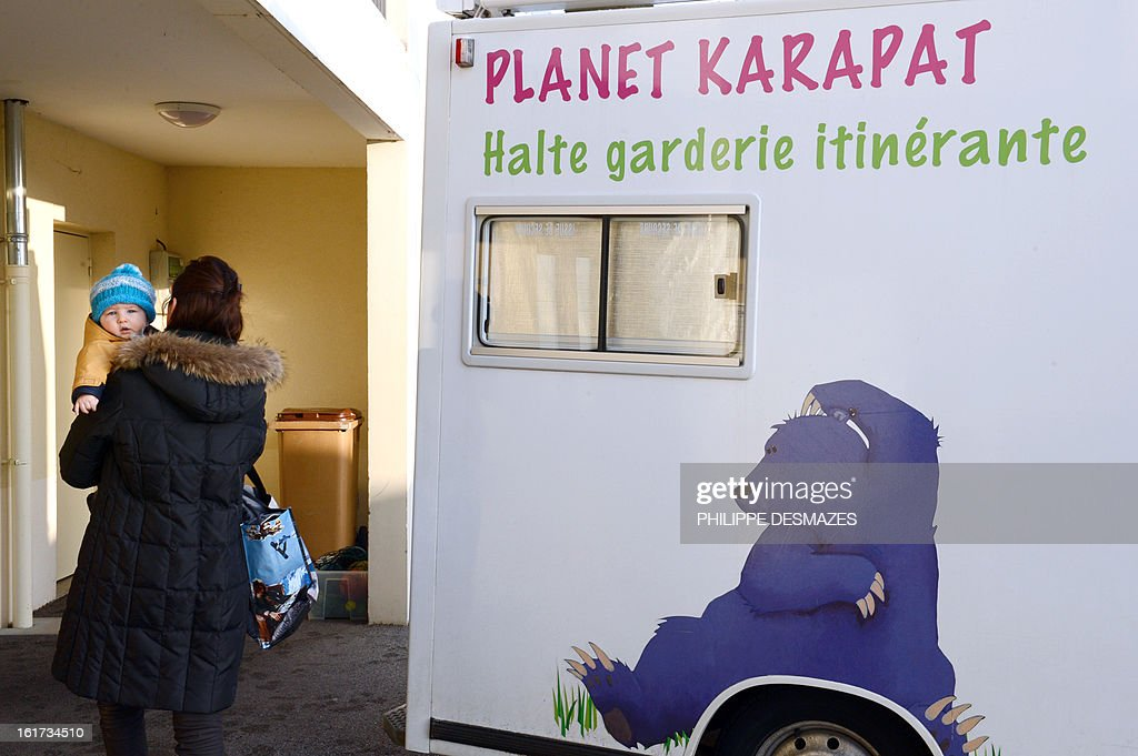 A woman brings her child to an itinerante creche of the Karapat association on February 8, 2012 in Lovagny.