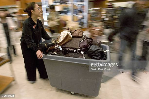 A woman brings in more handbags at Macy's department store on 'Black Friday' November 24 2006 in San Francisco California Many shoppers braved the...
