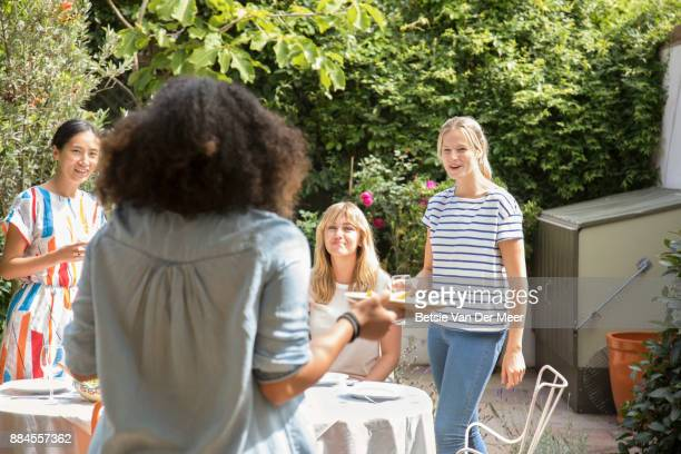 Woman brings out food to friends preparing table in garden.