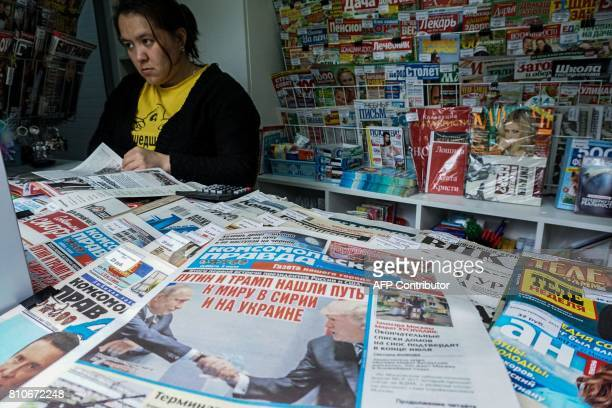 A woman browses a magazine in a newsstands by a newspaper featuring on the front page US President Donald Trump and Russian President Vladimir Putin...
