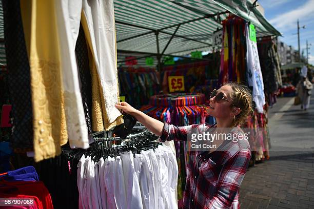 A woman browses clothes on sale at a stall in Walthamstow market on August 9 2016 in London England Walthamstow Market in north east London is...