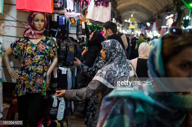 A woman browses clothing on display at a store inside the Grand Bazaar in Tehran Iran on Monday Aug 6 2018 Irans central bank acting on the eve of US...