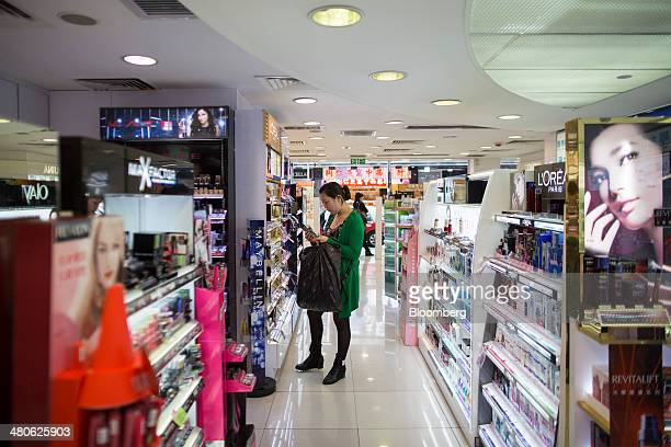 A woman browses cosmetic products in a Watsons store operated by AS Watson Co in the Tsim Sha Tsui district of Hong Kong China on Tuesday March 25...