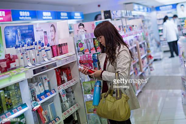 A woman browses cosmetics in a Watsons store operated by AS Watson Co in the Tsim Sha Tsui district of Hong Kong China on Tuesday March 25 2014...