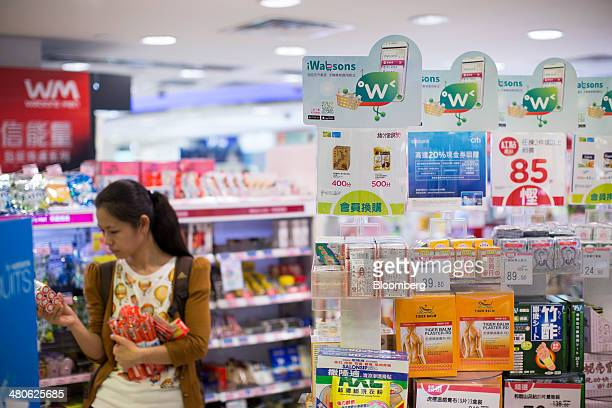A woman browses products behind a shelf for pain relief ointment and bandages in a Watsons store operated by AS Watson Co in the Tsim Sha Tsui...