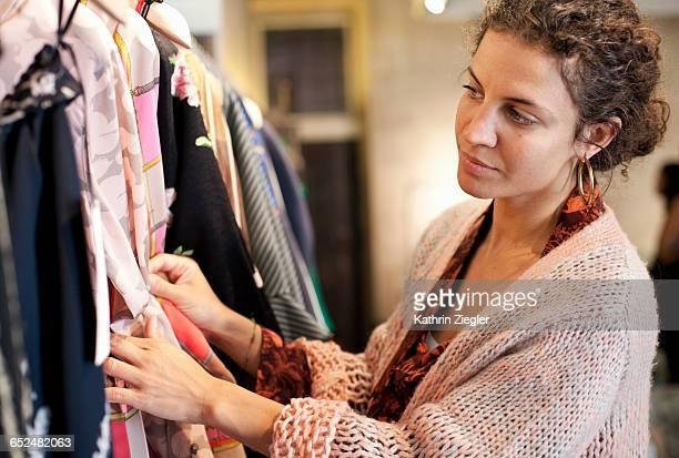 woman browsing clothing rack in shop