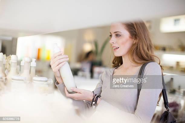 woman browsing products on display shelf - 化粧品 ストックフォトと画像
