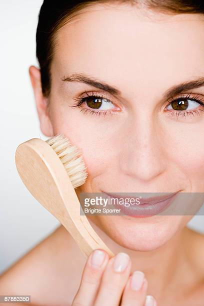 Woman brush massage her face
