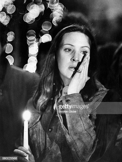 Woman brushes away a tear at a candle vigil for John Lennon on Boston Common on Dec. 9, 1980.