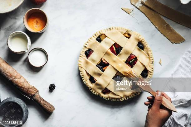 woman brushing a typical fruit lattice pie - sweet pie stock pictures, royalty-free photos & images
