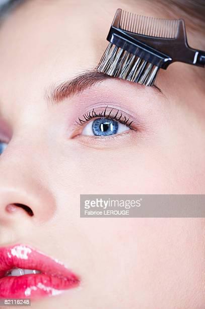 Woman brushing eyebrow
