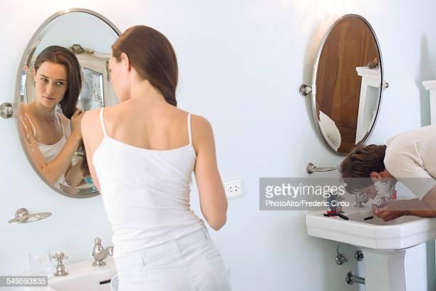 Woman brushing hair, husband shaving