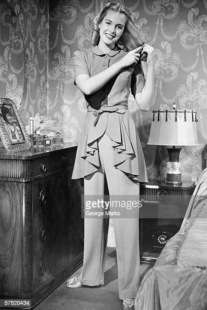 Woman brushing hair in bedroom, (B&W), portrait