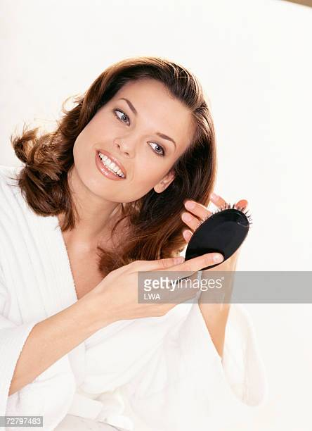 Woman brushing hair indoors