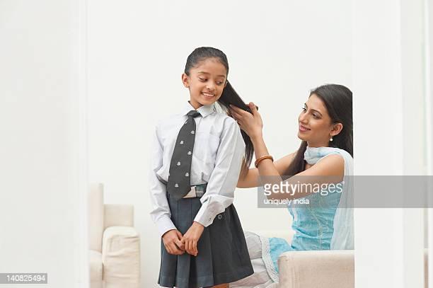 Woman brushing her daughter's hair