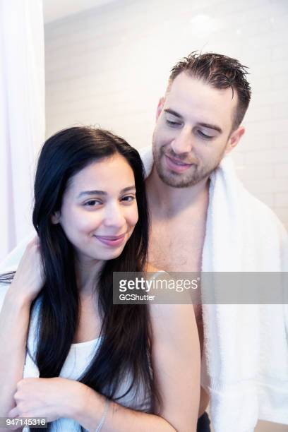 Woman brushing her hair as her boyfriend comes out from the shower and puts his arm around her.
