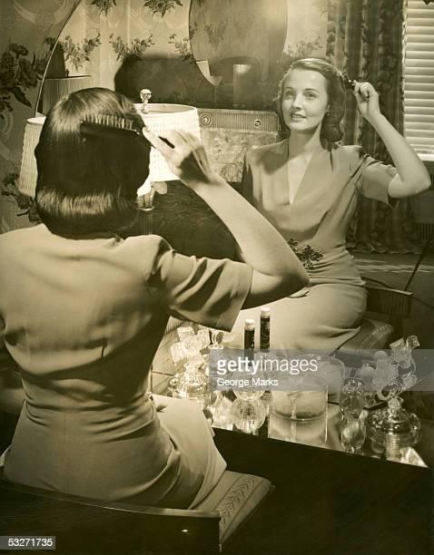 Woman brushing her hair at mirror