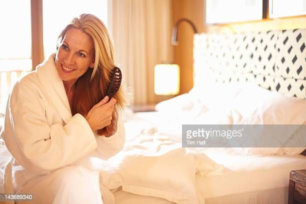 Woman brushing her hair on bed