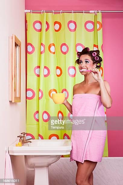Femme se brosser ses dents et fait une drôle de tête