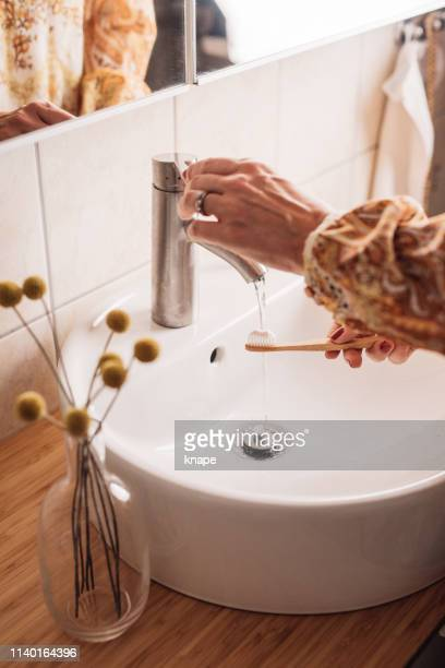 woman brushing teeth with eco friendly wooden toothbrush - water conservation stock pictures, royalty-free photos & images