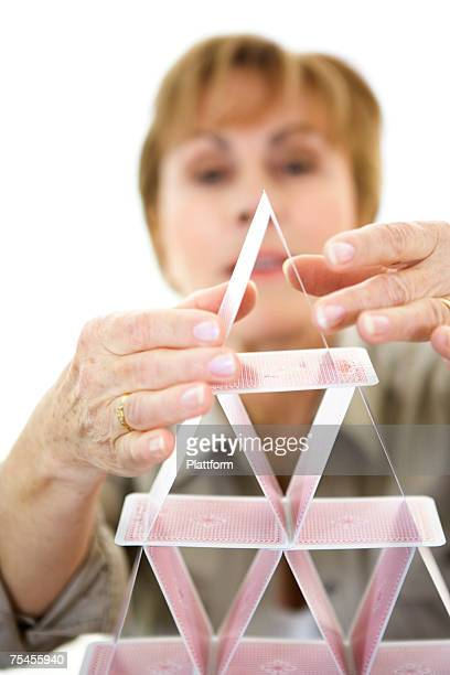 Woman building a house of cards.