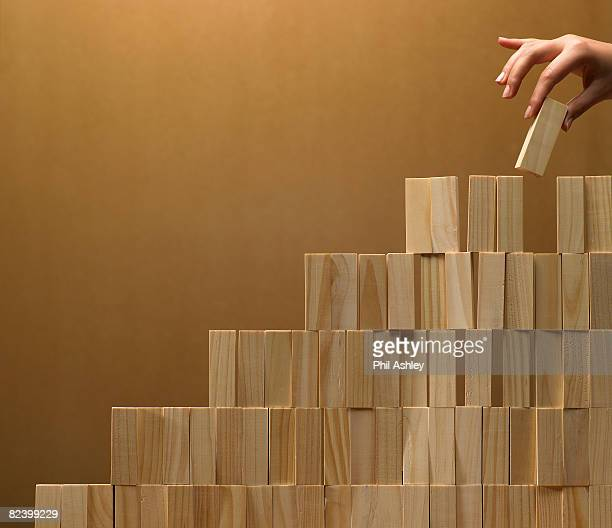 woman building a stack of wooden blocks